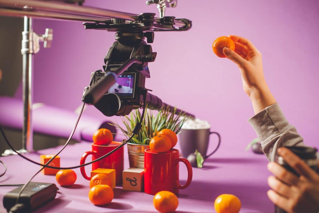 Purple set design with camera, tangerines, cups and hand