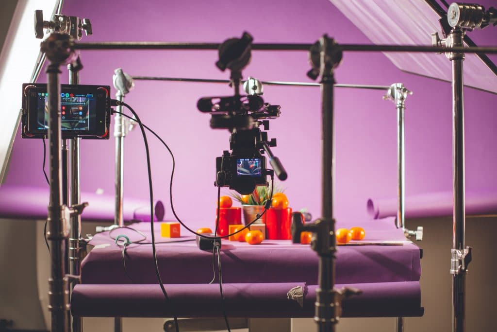 Camera stands in the purple filming set