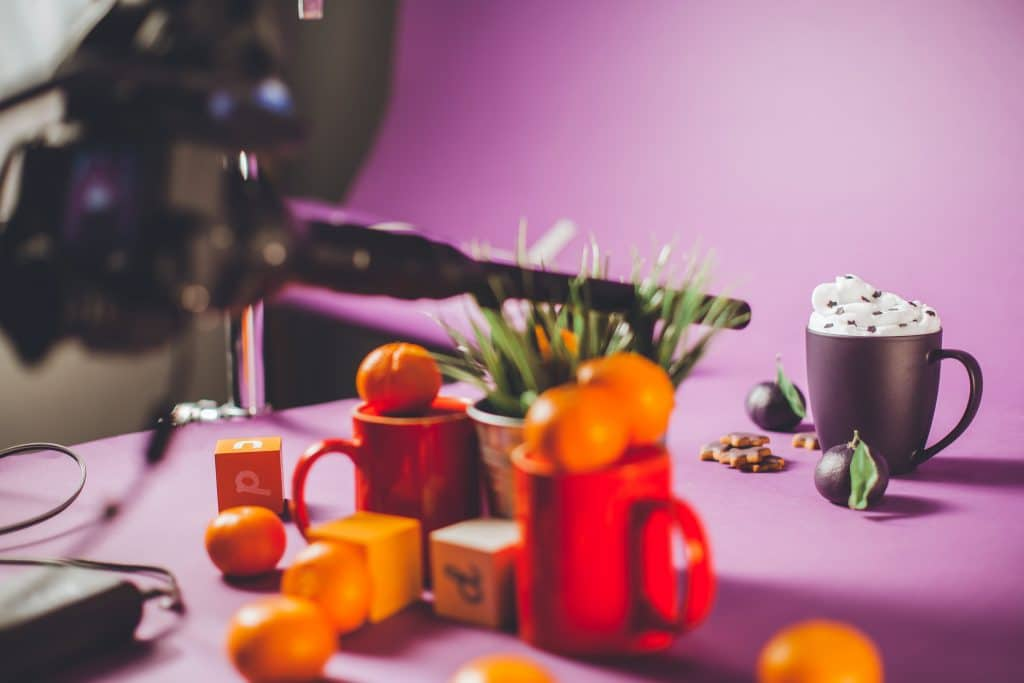 Purple filming set with cup, tangerines, camera